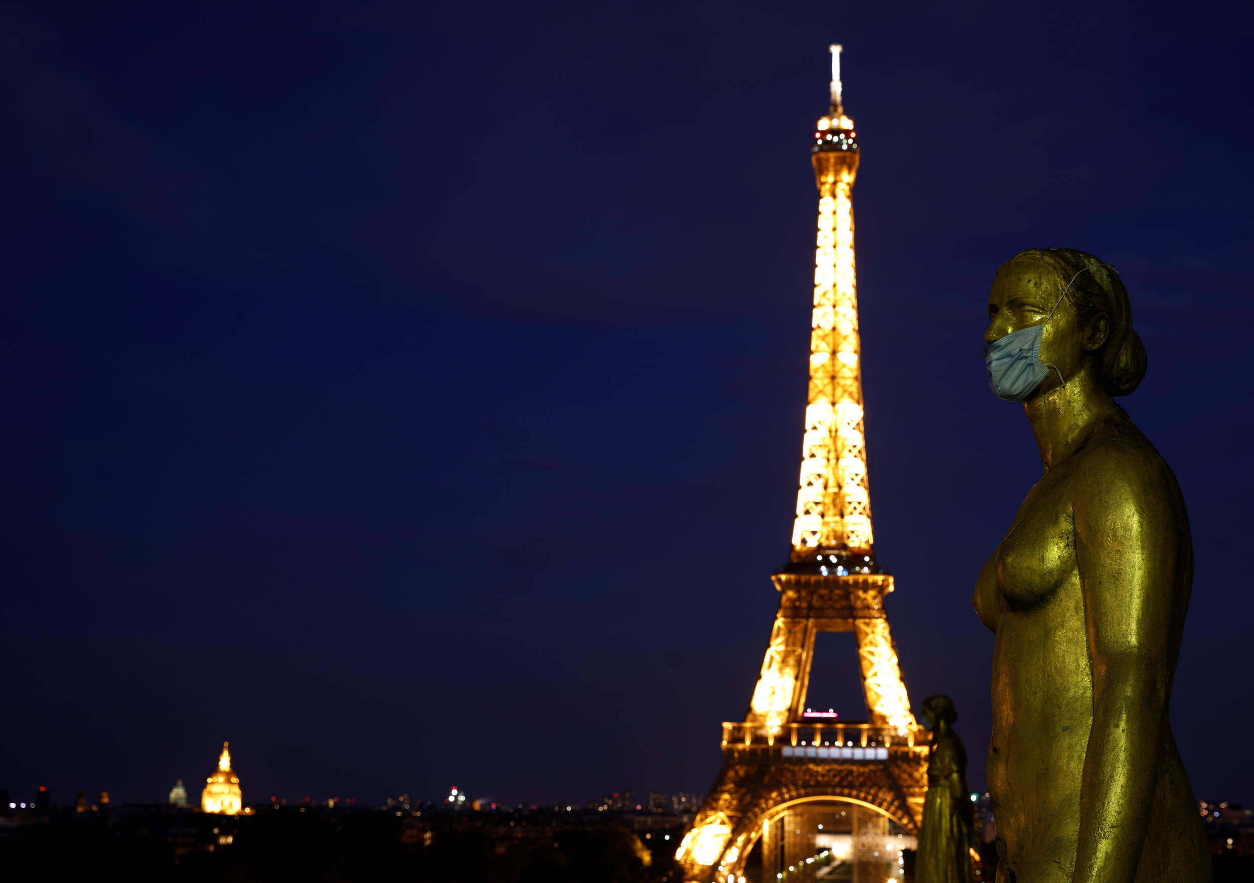 Golden Statues at the Trocadero square near the Eiffel tower wears a protective mask during the outbreak of the coronavirus disease (COVID-19) in Paris, France, May 2, 2020.