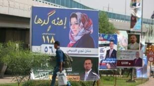 رجل يمر أمام لافتة انتخابية في بغداد في 8 أيار/مايو للمرشحة حنان نوري الربيعي