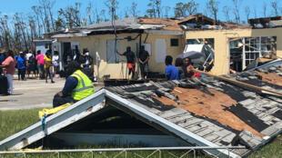 Sobrevivientes del huracán Dorian junto a un techo destruido, mientras esperan, durante horas al sol, vuelos a la isla de Bahamas, en el aeropuerto Treasure Cay en Abaco, el 5 de septiembre de 2019.
