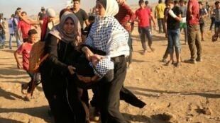 فلسطينيتان تنقلان أحد الجرحى خلال مظاهرة قرب حدود قطاع غزة في 14 أيلول/سبتمبر