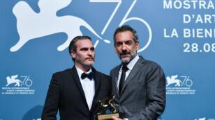"""L'acteur Joaquin Phoenix (à gauche) et le cinéaste américain Todd Philipps, après le couronnement de """"Joker"""" à la Mostra de Venise, le 7 septembre 2019."""