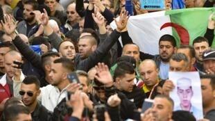 Des étudiants algériens hissant un drapeau national scandent des slogans lors de leur manifestation hebdomadaire anti-gouvernementale dans la capitale Alger, le 21 février 2020.