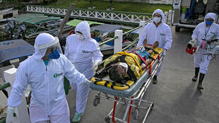 عاملون في المجال الصحي بنقلون مصابا بفيروس كورونا المستجدّ إلى سيارة الإسعاف في جزيرة ماراخو في البرازيل في 25 أيار/مايو 2020