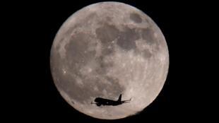 Un avión de pasajeros pasa frente a una luna llena minutos antes de aterrizar en el aeropuerto de Heathrow en Londres, Gran Bretaña, el 1 de enero de 2018.