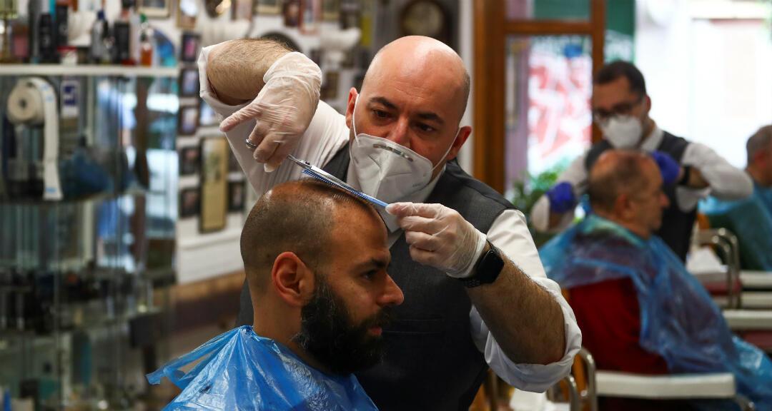 Un peluquero que usa mascarilla y guantes en la peluquería más antigua de Madrid, en el primer día de apertura durante la cuarentena por coronavirus. Madrid, España , el 4 de mayo de 2020.