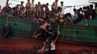 مهاجرون من الروهينغا ينقلون مساعدات غذائية ألقتها مروحيات في البحر في 14 آيار/مايو 2015