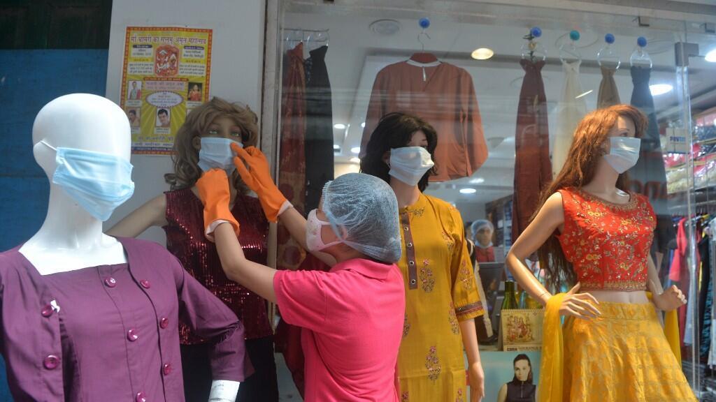 Una empleada arregla unos maniquíes ante la reapertura de los centros comerciales en Siliguri, India, el 6 de junio de 2020.
