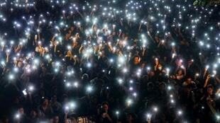 Des manifestants brandissent leurs téléphones portables allumés lors d'un rassemblement à Hong Kong le 5 juilllet 2019