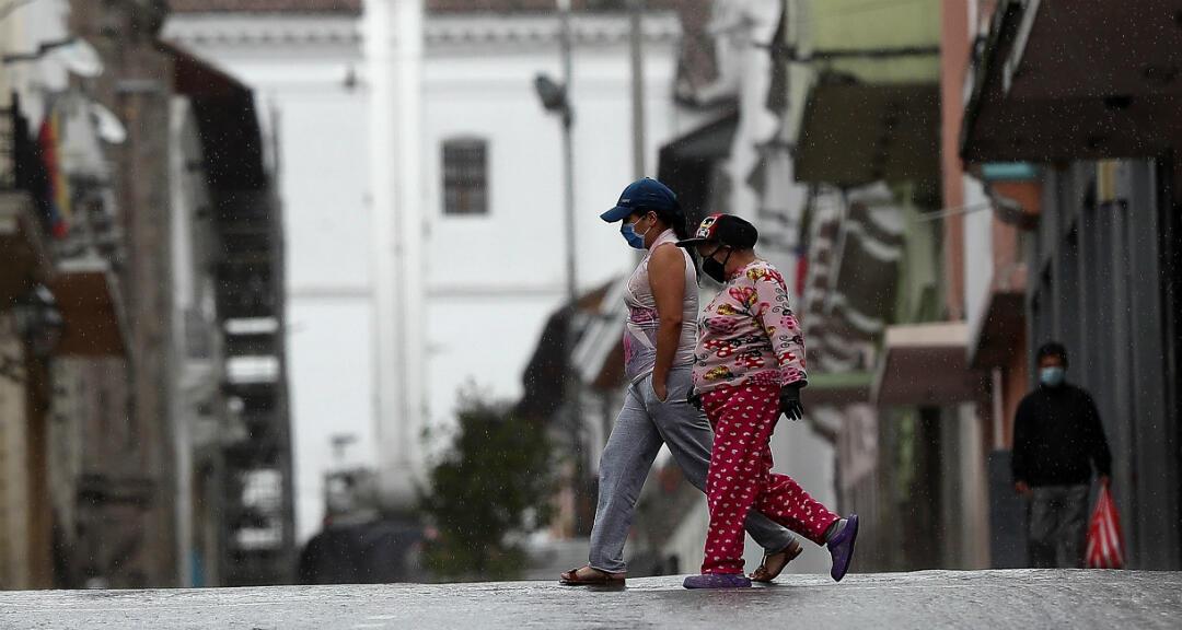 Dos mujeres cruzan una calle vacía en Quito, Ecuador el 3 de mayo de 2020.