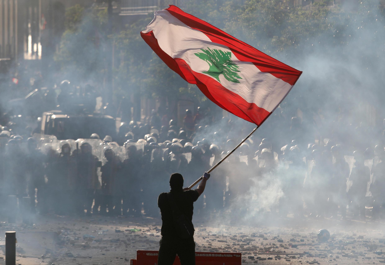 Un manifestante ondea la bandera libanesa frente a la policía antidisturbios durante una protesta en Beirut, Líbano, el 8 de agosto de 2020.