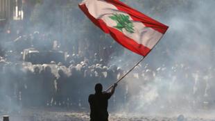 متظاهر يحمل العلم اللبناني بوجه القوى الأمنية في وسط العاصمة بيروت. 08/08/2020