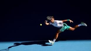 Serbia's Novak Djokovic hits a return against Frances Tiafoe of the US during their men's singles match on day three of the Australian Open tennis tournament in Melbourne on February 10, 2021.