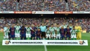 لاعبو برشلونة وريال بيتيس في صورة واحدة تعبيرا عن الأخوة وتكريما لضحايا الاعتداءين في برشلونة، في ملعب كامب نو الأحد 20 آب/أغسطس 2017