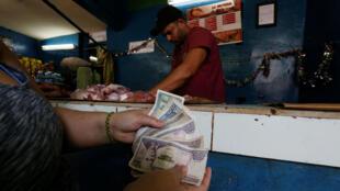 Una mujer muestra pesos cubanos convertibles, mientras compra en una carnicería local en La Habana, Cuba, el 30 de marzo de 2018.