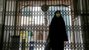 امرأة تمر أمام بوابة مسجد إمام زاده صالح المغلقة في طهران في 25 نيسان/أبريل 2020