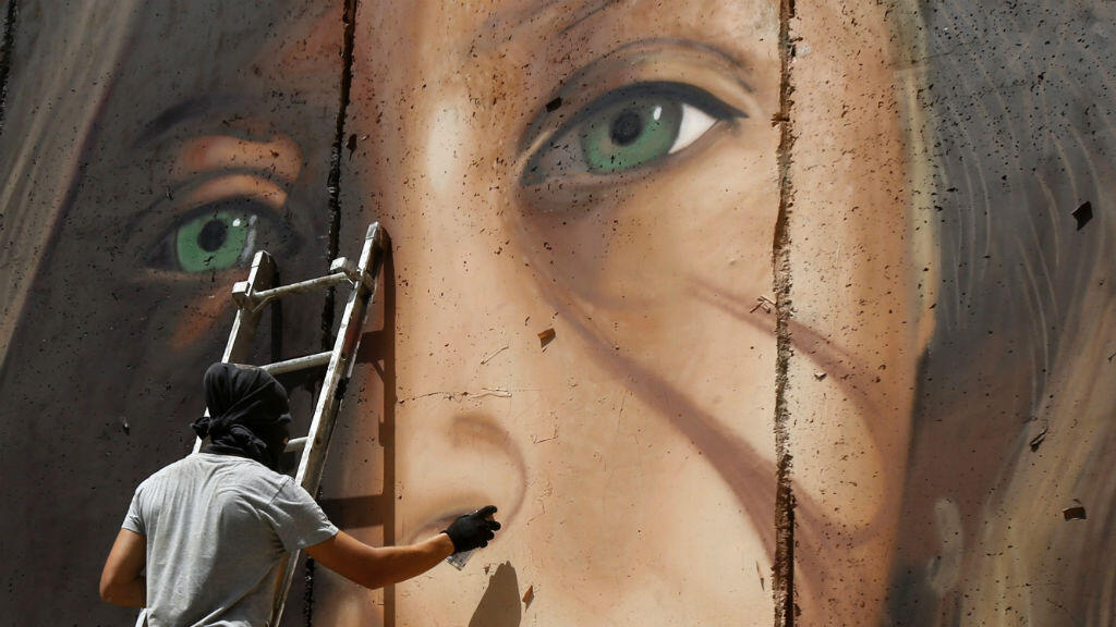 Italian artist Jorit Agoch (L) paints a mural depicting jailed Palestinian teenager Ahed Tamimi next to another artist on Israel's controversial separation barrier in the West Bank city of Bethlehem, on July 25,2018.