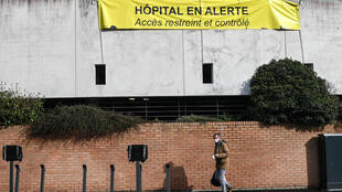 A man walks under a sign hanging outside the Dunkirk hospital center that read, 'Hospital on alert, access is controlled ' on February 17, 2021.