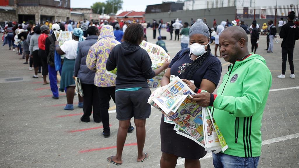 Un grupo de sudafricanos esperan para entrar en un supermercado, durante el confinamiento total que vive el país africano.