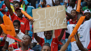 "A football fan holds a placard reading ""Stop Ebola in Africa"" ahead of the 2015 African Cup of Nations group A football match between Equatorial Guinea and Congo Barazville in Bata on January 17, 2015."