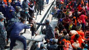 أفراد من البحرية البنغلاديشية يساعدون طفلا لاجئا من الروهينغا على النزول من سفينة تابعة للبحرية عند وصولهم إلى جزيرة بهاسان شار في منطقة نواكالي، 29  كانون الأول/ديسمبر 2020.