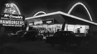 """En 1955, Ray Kroc ouvre le """"McDonald's numéro 1"""" à Des Plaines, dans l'Illinois, orné des arches dorées."""