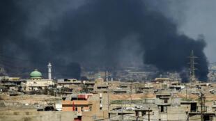 De la fumée s'élève au-dessus de la partie Ouest de Mossoul le 24 mars 2017, durant une offensive des forces irakiennes.