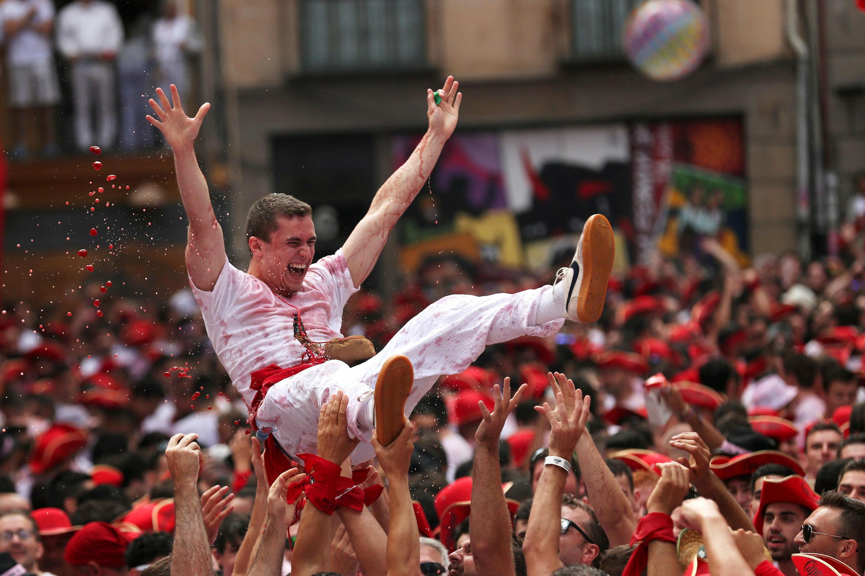 Un joven es arrojado al aire por otros durante la inauguración del festival de San Fermín en Pamplona, España, el 6 de julio de 2018.