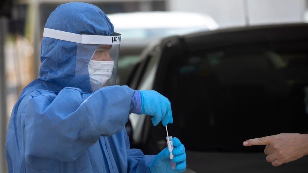 Un trabajador de salud israelí realiza una prueba de coronavirus en un centro de pruebas de manejo en Tel Aviv, Israel, el lunes 6 de julio de 2020.