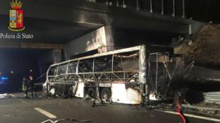 رجال الإطفاء يقفون بجوار حطام حافلة تقل مراهقين مجريين بعد أن اصطدمت بعمود واشتعلت فيها النيران.