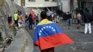 Un manifestante antigubernamental está envuelto en una bandera venezolana durante enfrentamientos con la policía y las tropas en los alrededores de un puesto de comando de la Guardia Nacional en Cotiza, norte de Caracas, el 21 de enero de 2019.