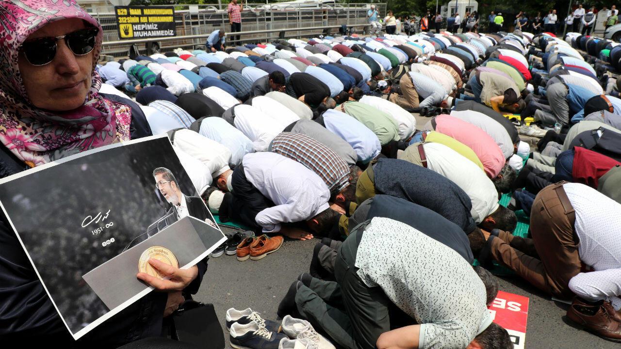 Una mujer sostiene una foto del presidente egipcio Mohamed Morsi mientras la gente reza durante un funeral simbólico el 18 de junio de 2019 frente a la embajada en Ankara.