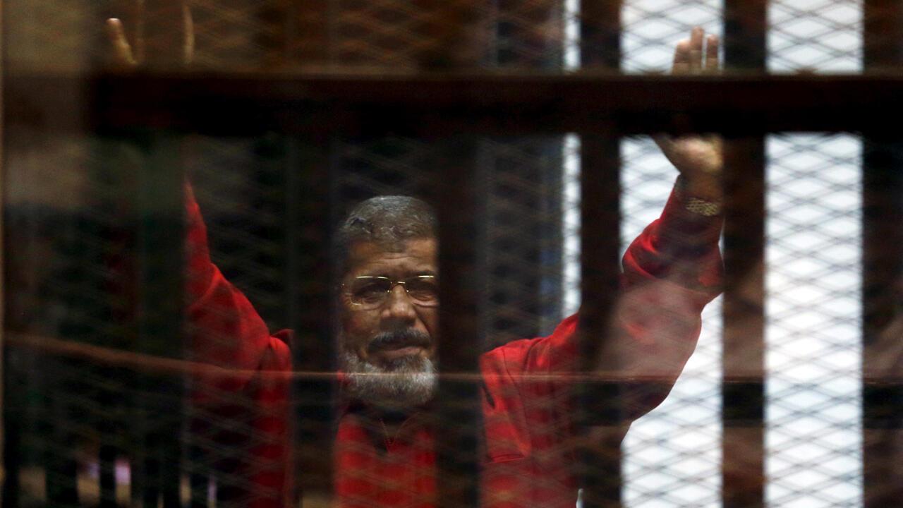 El depuesto presidente de Egipto, Mohamed Morsi, saluda a sus abogados detrás de las rejas durante su comparecencia ante un tribunal en El Cairo, Egipto, el 21 de junio de 2015.