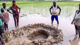 Photo prise le 22 juillet 2019 de villageois autour du cratère d'une possible météorite tombée dans un champ dans l'est de l'Inde