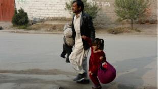 """رجل وطفلاه يهربان إثر الهجوم على مقر منظمة """"أنقذوا الأطفال"""" في جلال آباد 24 يناير/كانون الثاني 2018"""