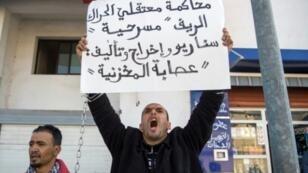 مغربي يرفع لافتة تتهم المسؤولين بفبركة محاكمة أنصار الحراك أثناء انعقاد جلسة محكمة استئناف الدار البيضاء في 5 كانون الثاني/يناير 2018