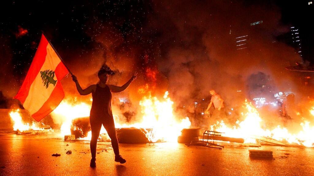 Una manifestante antigubernamental lleva una bandera libanesa mientras que otros manifestantes queman neumáticos y bloquean la carretera principal durante una protesta contra la condición económica, el colapso de la libra libanesa y el aumento de los precios al bloquear la carretera en la zona de Jal El Dib al norte de Beirut, Líbano, 11 de junio de 2020.