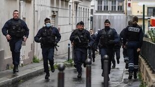 French police officers rush to the scene after people were injured near the former offices of the French satirical magazine Charlie Hebdo following an attack by a man wielding a knife in the capital Paris on September 25, 2020