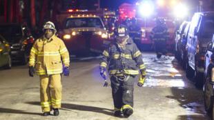 Des pompiers marchent dans la rue de l'immeuble où a eu lieu l'incendie qui a fait 12 morts, jeudi 28 décembre 2017, à New York.