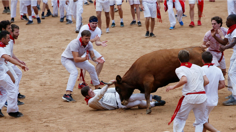 Uno de los asistentes a la fiesta es arrojado por una vaquilla después del primer encierro de los toros en las Fiestas de San Fermín en Pamplona, España, el 7 de julio de 2018.