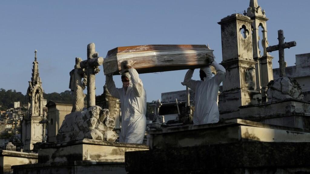 Sepultureros llevan el ataúd de por coronavirus durante su funeral, en Río de Janeiro, Brasil, 18 de mayo de 2020.