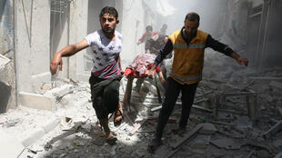 Des hommes portent un blessé après des bombardements dans la grande ville du Nord, Alep, le 29 avril 2016.