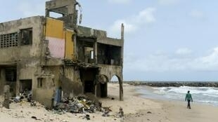 The shore-hugging Alpha Beach road has disappeared under the waves and apartment blocks built with prized ocean views just 10 years ago are now occupied only by squatters