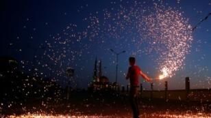 شاب فلسطيني يلوح بمشعل قرب مسجد في غزة في 16 أيار/مايو 2018.