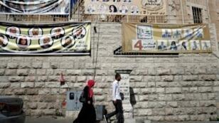 مارة أمام لافتات تحمل صور مرشحين للانتخابات البلدية في بيت لحم في 10 ايار/مايو 2017