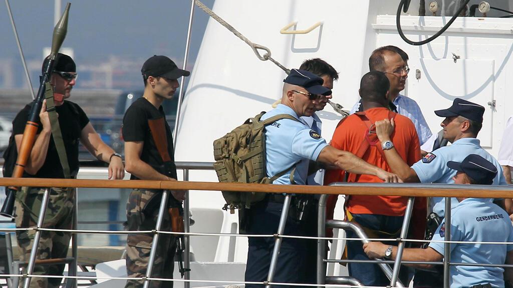 Des gendarmes français et un suspect lors de la reconstitution de la libération du Ponant, à Nice, en juillet 2010.