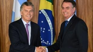 Argentina's President Mauricio Macri (L) and Brazilian President Jair Bolsonaro shake hands after signing an agreement at Planalto Palace in Brasilia, on January 16, 2019