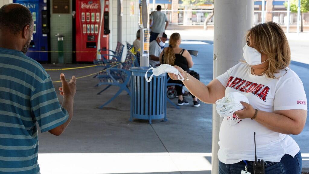 Un empleado de Sun Tran ofrece máscaras gratuitas a los pasajeros para prevenir la propagación de coronavirus, en la estación de autobuses del centro de Tucson, Arizona, EE. UU., 20 de junio de 2020.