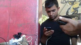 Un migrant consulte son téléphone, qui lui permet de rester en contact avec ses proches.