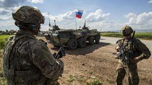 US soldiers stand along the side of a road across near a Russian military armoured personnel carrier (APC), near the village of Tannuriyah in the countryside east of Qamishli in Syria's northeastern Hasakah province on May 2, 2020