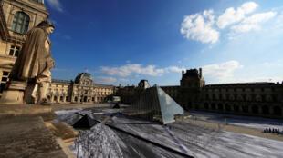 Vista general de la obra de arte del artista francés JR alrededor de la pirámide de vidrio del Louvre.